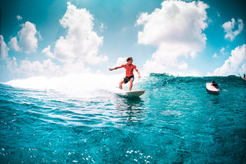 Wall Mural - Surfer in red shirt rides the ocean wave