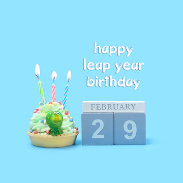 Happy Leap year Birthday greeting concept. February 29 date calendar, Frog and Birthday cupcakes on blue background. Leap day leap year