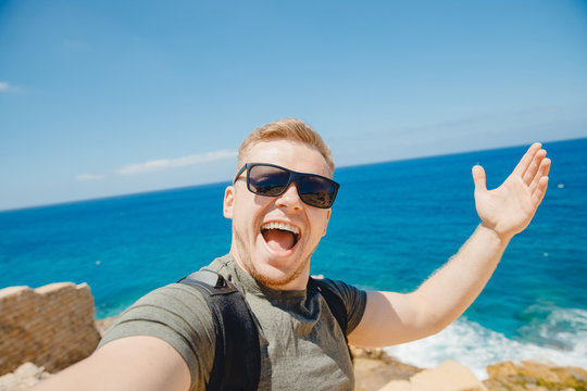 Happy traveler man taking selfie photo in sunglasses on background of bruise sea with backpack. Travel concept
