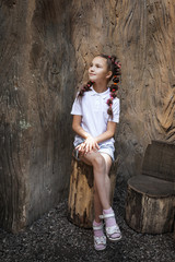 pretty lovely small girl with pigtails wearing white shirt sitting on the stump near the stem of the tree in the park