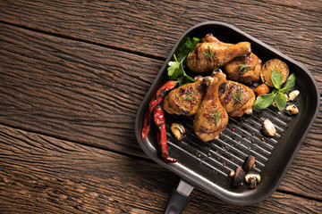 Fototapete - Grilled chicken leg with various vegetables on pan on old wooden background