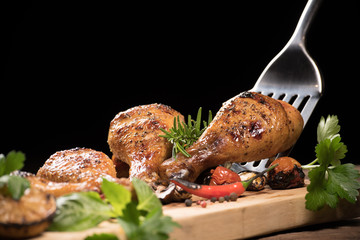 Wall Mural - Roasted chicken leg and various vegetables on a chopping board ..
