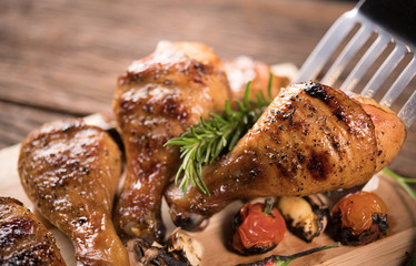 Fototapete - Roasted chicken leg and various vegetables on a chopping board ..