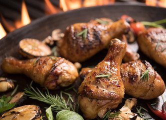 Fototapete - Grilled chicken leg with various vegetables on pan on the flaming grill
