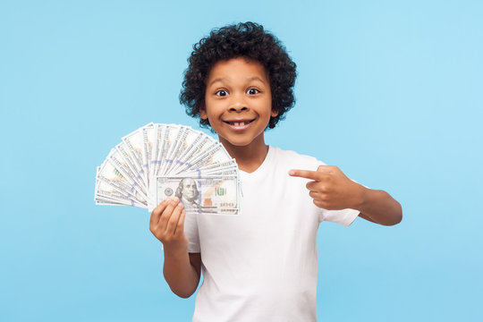 I'm rich! Joyful lucky wealthy little boy with curly hair pointing to fan of dollar banknotes, boasting money and looking at camera with excited toothy smile. indoor studio shot, blue background