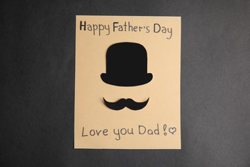 Greeting card with phrase HAPPY FATHER'S DAY I LOVE YOU DAD on black background, top view