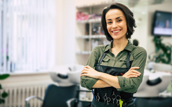 Smile of the professional. Portrait of a gorgeous young hairstylist standing with folded arms near her workplace in the salon.