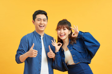 Excited beautiful asian couple shows thumb up gesture agree to do something and collaborate against orange wall, did great job, show approval, like idea. Everything will be OK. Fotomurales