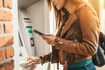 Close up shot of young adult woman. He typing pin code on keypad of ATM machine while using smart phone. Fotomurales