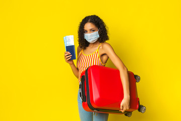 Girl mulatto tourist with a medical mask against a viral infection, coronavirus 2020, holding a passport with plane tickets and a suitcase. The concept of prevention Fotomurales
