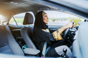 Young gorgeous smiling muslim woman in traditional wear driving her expensive car. Wall mural