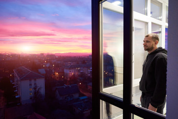 Side view of a man standing on a balcony with panoramic windows and looking into the distance while enjoying magical sunset. Urban landscape from height and a multi-colored fiery sky with setting sun Wall mural