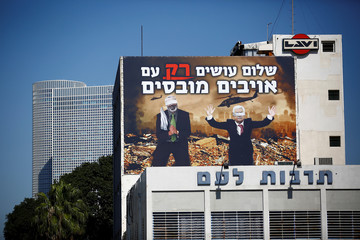 A billboard over a Tel Aviv highway shows photoshopped warzone images of Palestinian President Mahmoud Abbas and Hamas leader Ismail Haniyeh, both blindfolded, with a slogan