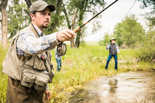 Grandfather, father and son fly fishing on small stream. Red Lodge, Montana, USA