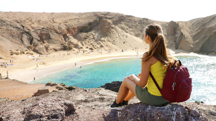 Beautiful young backpacker admiring Playa Papagayo beach in Lanzarote, Canary Islands, Spain
