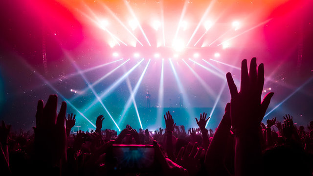 Happy people dance in nightclub DJ party concert and listen to electronic dancing music from DJ on the stage. Silhouette cheerful crowd celebrate New Year party 2020. People lifestyle DJ nightlife.