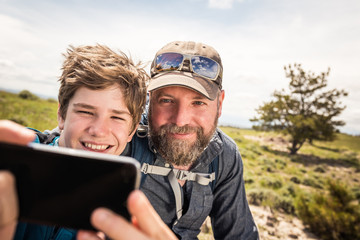 Father and son having fun taking selfie while hiking in rural prairie landscape. Cody, Wyoming, USA