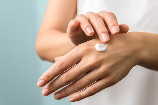 healthy hands and nails. seasonal skin protection. woman applying moisturizer on her hands