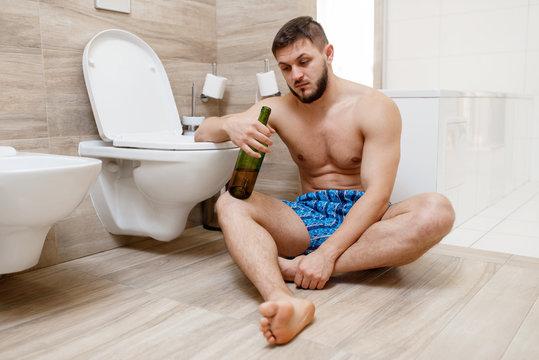 Hangover man sitting on the floor in bathroom