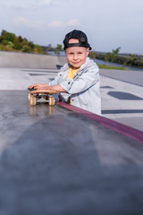 Little boy child 4-5 years old, in summer in city. Rest on weekend. Emotions of fun joy and happiness. Free space for copy text. Sports ground, skateboard, fitness and sports training.