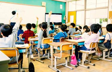 小学校の教室で手を挙げる生徒