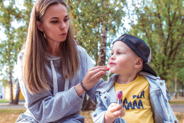 Woman mom wipes child cheeks and lips with ice-cream from ice cream, in summer in park, little boy eats ice cream. Casual wear. Caring parenting help and support son.