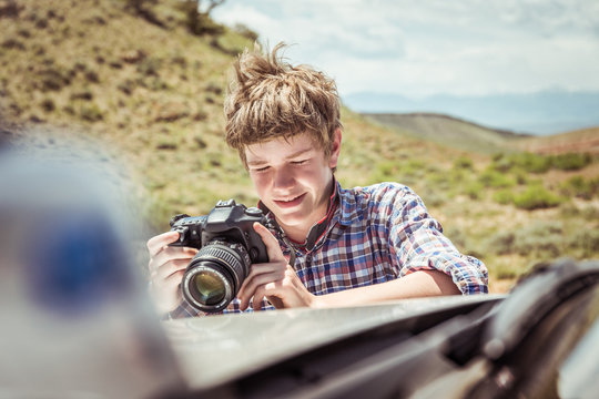 Father and son out in nature, having fun taking pictures and camping in truck. Bridger, Montana, USA