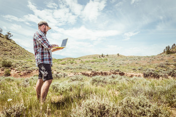 Man surveying and studying a rural prairie setting. Bridger, Montana, USA