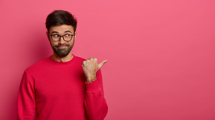 Pick best choice. Cheerful unshaven man brags item on sale in mall, points thumb and recommends product, wears casual red jumper, isolated over rosy background. Check it out, promotion concept