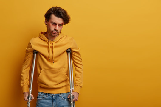 Frustrated man with injured face learns to walk again, needs to see surgeon, stands on crutches, has recovery period after terrible accident, concentrated down, isolated on yellow wall, blank space