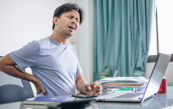 Young Asian office worker suffering from back pain in office , Office syndrome