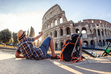 Happy young man tourist wearing shirt and hat with bike taking pictures with vintage camera at colosseum in Rome, Italy at sunrise.