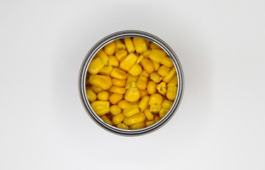 Top view close up on isolated open metal can with yellow sweet corn, blank white background