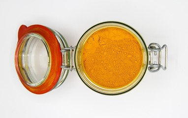 Top view on opening of isolated preserving glass jar with red rubber ring and yellow turmeric curcuma powder, white blank background