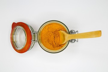 Top view on opening of isolated preserving glass jar with red rubber ring and yellow turmeric curcuma powder, wood spoon, white blank background