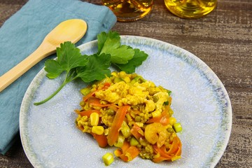 Close up of thai fried rice dish with eggs, peas, sweet corn, shrimps and carrots on wood table