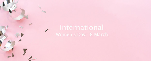 close up on group of silver color of rolling ribbon and confetti on pink background with message international women's day 8 march concept