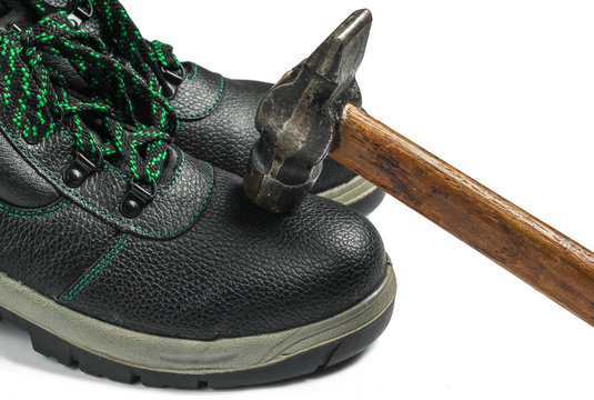 Work leather shoes and hammer on a white background. Strength check, worker safety
