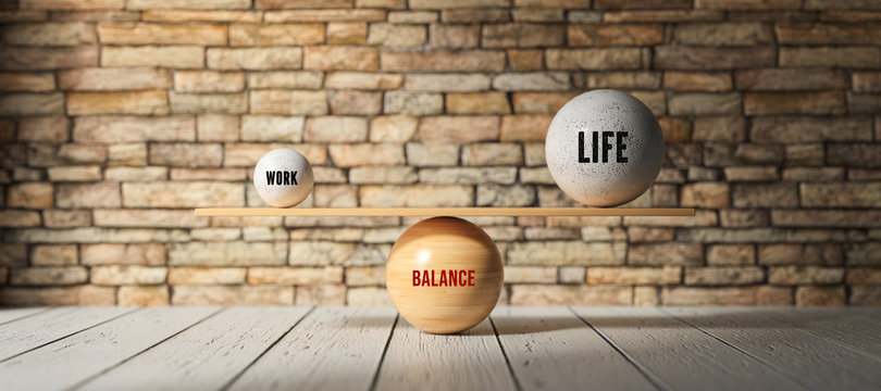 spheres forming scale with the words WORK, LIFE and BALANCE on wooden floor in front of brick wall