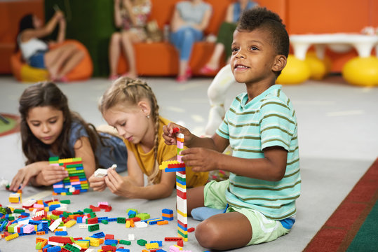 Kids playing block toys in playroom at nursery. Four children playing constructor while laying on the floor. Fun in kids room.