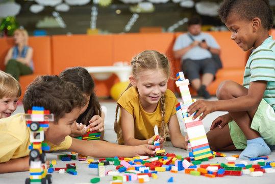 Children building blocks in kindergarten. Indoor games and activities. Kids care school.