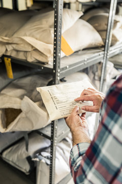 Close-up of farmer inspecting a bag of grass seeds in storage shelf. Montana, USA