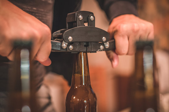 Detail of a tool for closing or bottling beer bottles. Man closing a beer bottle with a cap. Tool for closing craft beer bottle.