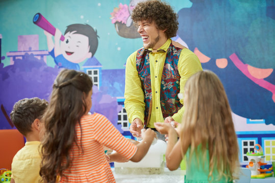 Cheerful entertainer doing science show for kids. Children having fun participating in science experiment. Kids entertainment and education.
