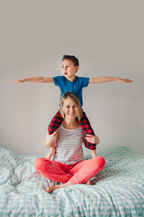Smiling Caucasian mother and boy son playing in bedroom at home. Child sitting on moms shoulders and laughing. Family having fun together. Happy childhood candid authentic lifestyle.