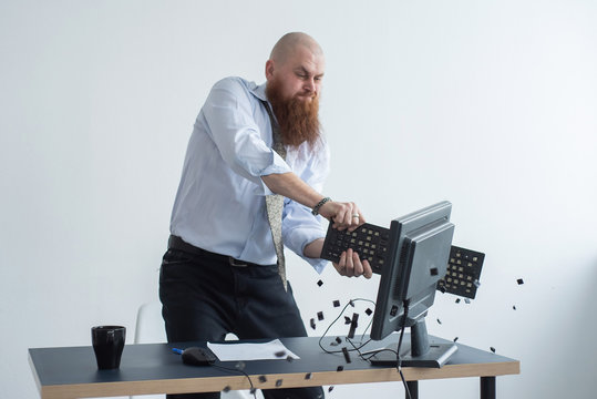 Angry bald man with a red beard in the office in a business suit crashes a computer. Manager with a nervous breakdown breaks the keyboard on the monitor.