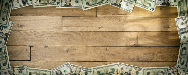 Banner sized background of used dollar banknotes lying on wooden floor. Focus on lower part.