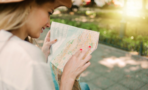 Blonde woman in a felt hat looks at city map in unfamiliar city outdoor