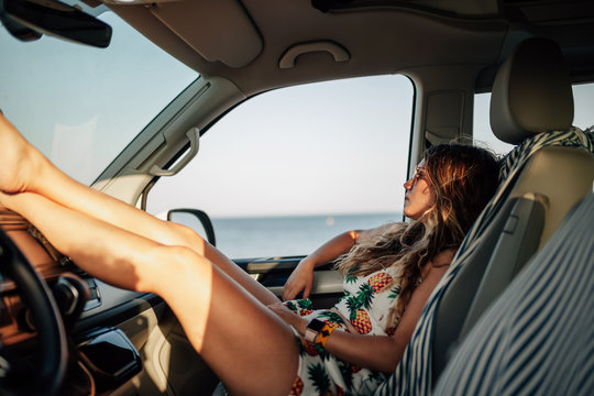Woman sitting in the driver's seat in a van with mini skirt