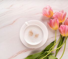 Cup of coffee and pink tulips top view on marble background